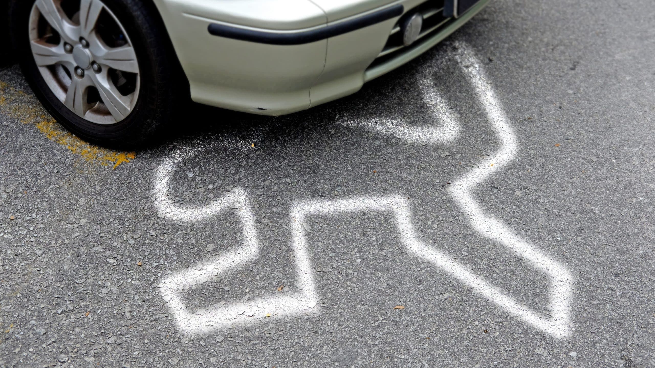 Car accident scene with chalk outline victim under.