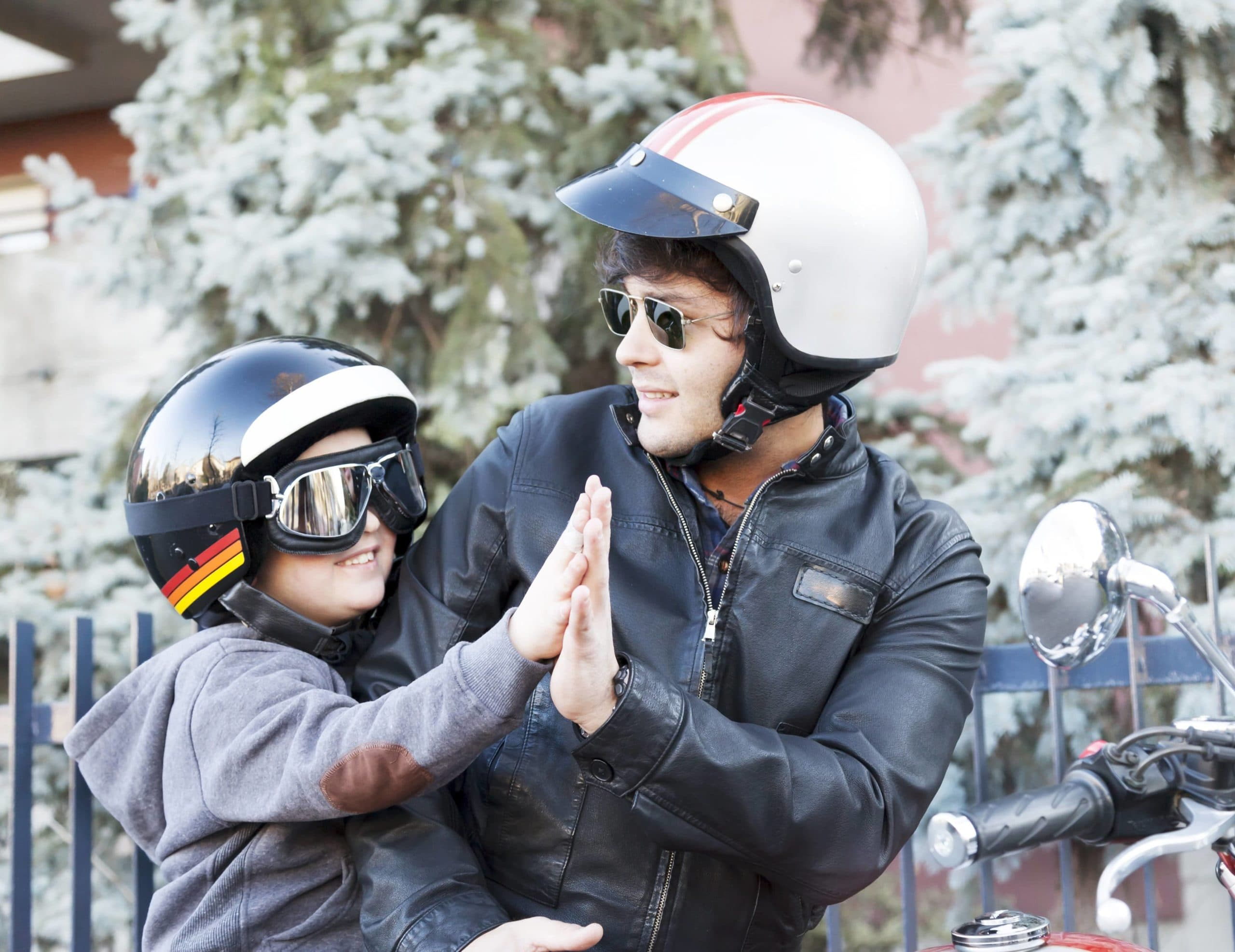Kid on motorcycle wearing helmet and goggles for safety.
