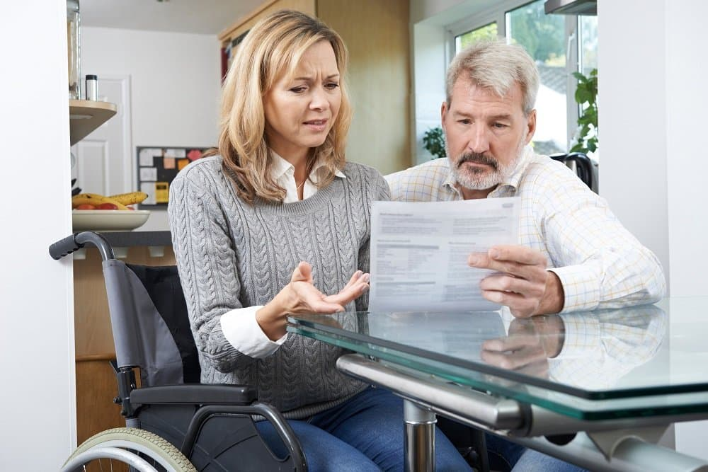 Woman in wheelchair reading her social disability benefits claim.