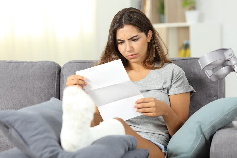 Injured woman reading document for workers injury claim.